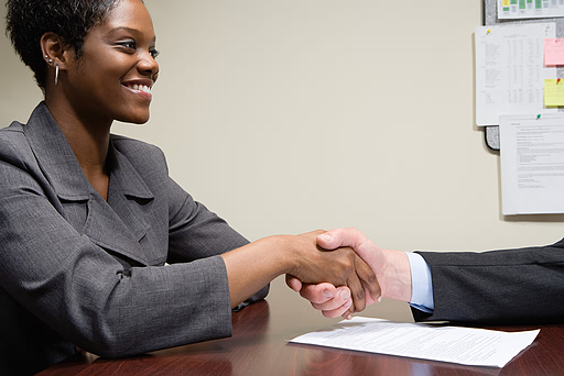 Image: African-American woman shaking hands with Caucasian man