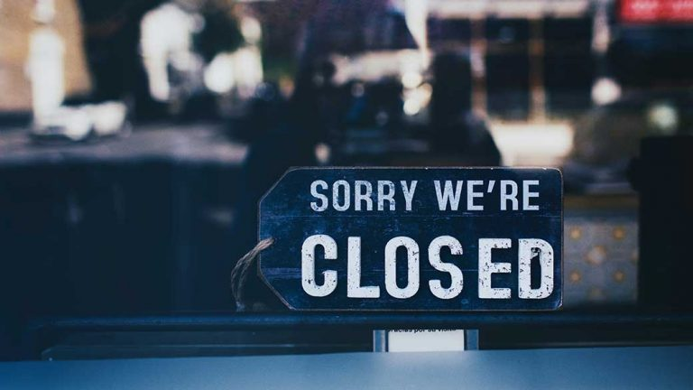 image: business storefront with a sorry we're closed sign